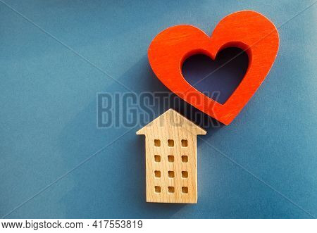 Wooden House And Red Heart On A Blue Background. Concept Of Sweet Home. Property Insurance. A New Ho