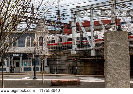 NORWALK, CT,USA  - APRIL 16, 2021:  Rail road bridge with train view from Washington Street in spring day