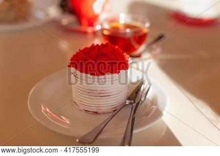 Festive Dessert, Red Velvet Cake On Table In Cafe, In Sunlight. Single Round Cake Topped With Sponge