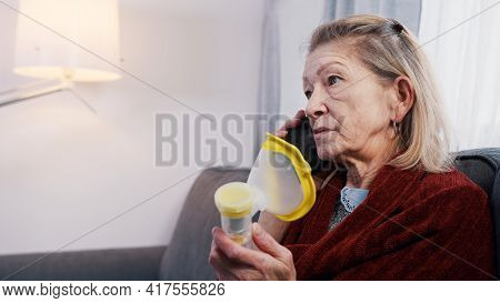 Elderly Woman Using Oxygen Inhaler While Having A Phone Call. Vulnerable Person During Covid Outbrea
