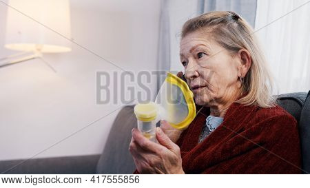 Vulnerable Old Woman Having A Phone Call And Using Inhaler. Difficulty Breathing At Old Age. High Qu