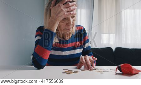 Poor Old Woman Counting Coins On The Table. Hopeless Elderly Lady With Financial Problems. High Qual