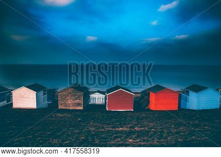 Colorful beach huts with stormy blue sky, beach of Tankerton near Whitstable in Kent, UK
