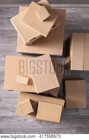 Stack of cardboard box on floor laminate background. Cardboard boxes for moving to new home. Relocation concept  top view