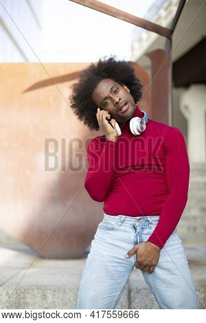Portrait Of Young African American Man Talking On Phone In Provocative Gesture. He Is Outdoors. Spac