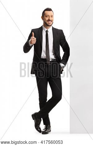 Full length portrait of a young professional man leaning on a wall and showing thumbs up isolated on white background