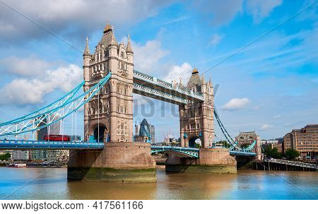 Tower Bridge On A Bright Sunny Day With Blue Sky And Clouds. Calm Water With Reflections. London, En