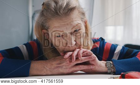 Desperate Old Woman Pensioner Looking At Small Amount Of Coins On The Table. High Quality Photo