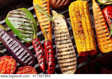 Grilled vegetables cooking on grill with spices and herbs. Top view