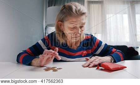 Old Retired Woman Desperately Counting Coins Left. High Quality Photo