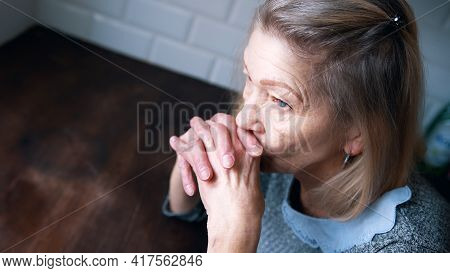 Pensive Lonely Depressed Elderly Woman In Her Home. High Quality Photo