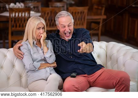 Man having a good laughter, his wife cries while watching the same tv program, lack of empathy concept