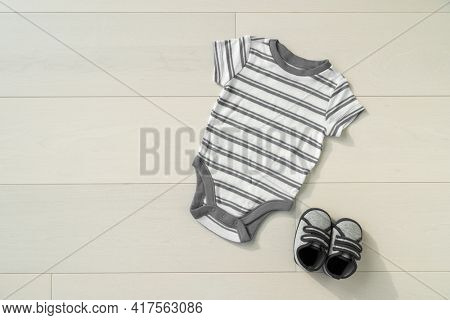 Grey baby clothes and shoes on wooden floor background. Organic cotton eco friendly clothing sustainable kids outfits.
