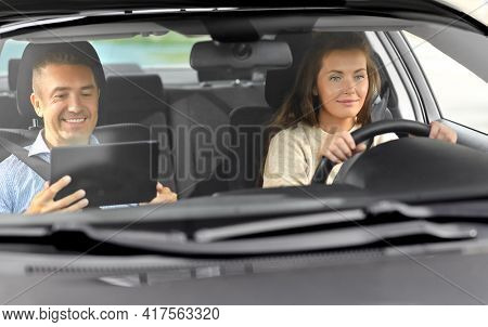 driver courses and people concept - woman and driving school instructor with tablet computer talking in car