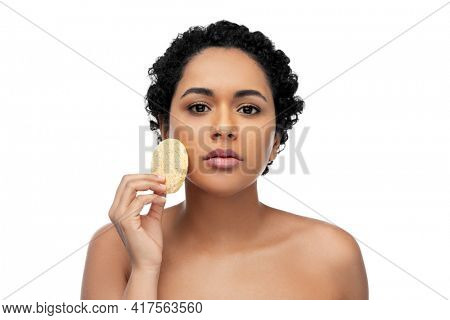 beauty, people and skincare concept - young african american woman with bare shoulders cleaning face with exfoliating sponge over white background