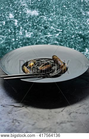 Seafood black spaghetti pasta with clams served on black plate on dark stone