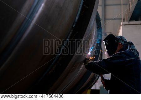 A Welder Welds Large Diameter Pipes With Manual Electric Arc Welding. Mma Or Mmaw Welding.