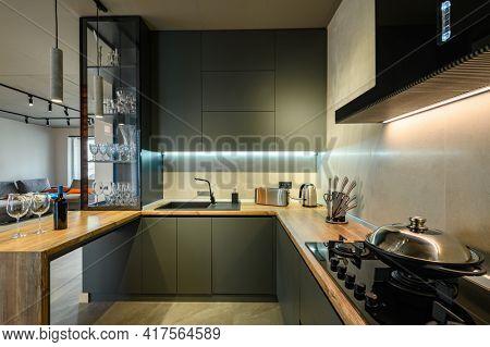 Modern large luxury dark gray kitchen closeup with wine bottle at kitchen counter, low key
