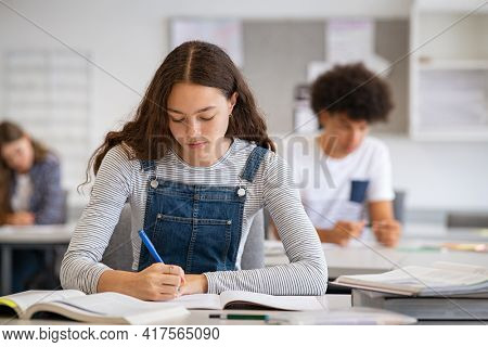 High school student taking notes from book for her study. Young woman sitting at desk and finding information in college library. Focused girl studying in classroom completing assignment.