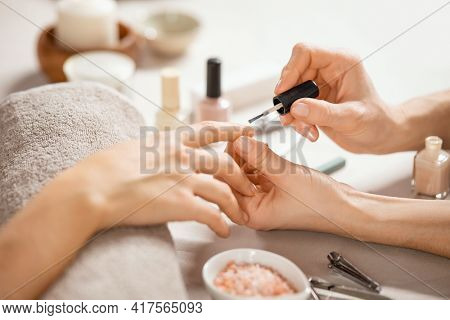 Close up of a beautician applying nail polish to female hand in a nail salon. Woman hand applying pink polish after the manicure at spa. Detail of woman applying nail varnish to finger client.