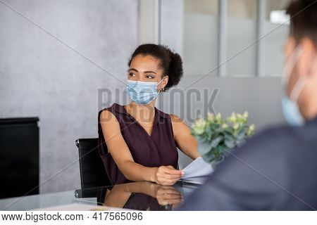 Mixed race businesswoman wearing face mask during meeting at office against coronavirus. African business employee working while wearing protective face mask for safety against covid-19 pandemic.