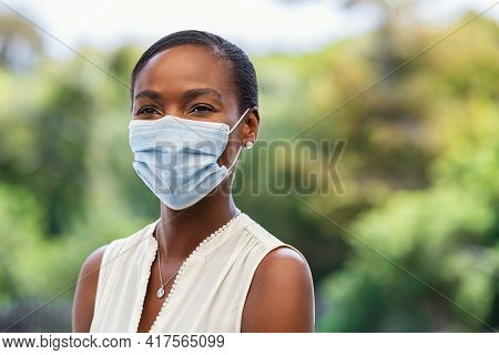 Mature african american woman wearing covid-19 protective face mask. Beautiful black woman in park wearing surgical mask for safety against coronavirus with copy space. Mid adult happy female portrait