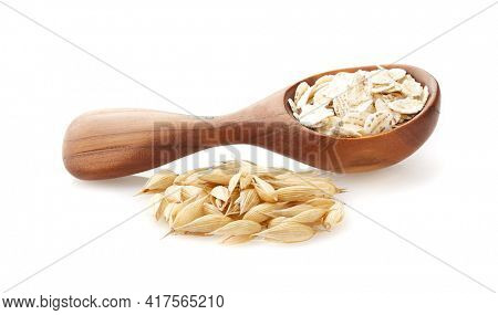 Oats flakes in wooden spoon with oats plant isolated on white background