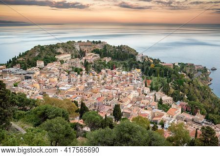 Picturesque Taormina town at sunset in Sicily, Italy. Beautiful top view of the Taormina city