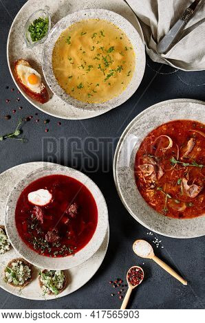 Soups Set - Chicken and Noodle Soup, Borscht (beet soup) and Solyanka (spicy and sour soup). Dinner set on dark rustic table. Top view, flat lay