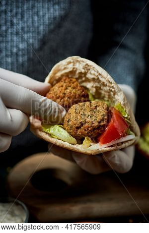 closeup of a young man, wearing latex gloves, filling a pita bread with some falafel and chopped lettuce, onion and tomato