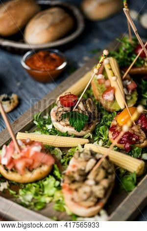 closeup of a wooden tray, with some different vegan spanish pinchos, made with bread with different toppings, served as snacks or appetizers, on a gray rustic wooden table