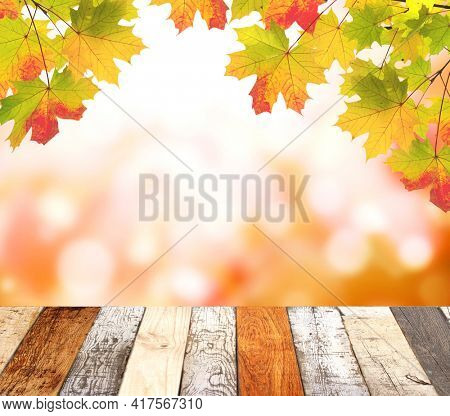 Old wooden desk with nature fall background. Vintage wooden table top and maple leaves on blurred autumn backdrop. Mock up template. Copy space for text