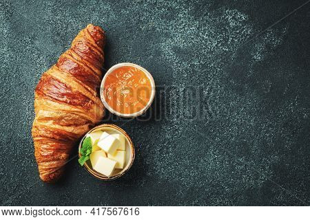 Fresh Sweet Croissant With Butter And Orange Jam For Breakfast. Continental Breakfast On A Black Con