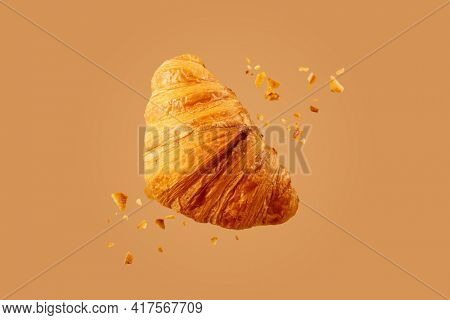 Freshly baked croissant flying in air. Close up of crumbled french croissant.