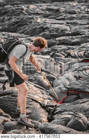 Volcanic eruption Hawaii volcano hike adventure guided tour. Man poking lava walking with backpack on black rock in Big Island, Hawaii.