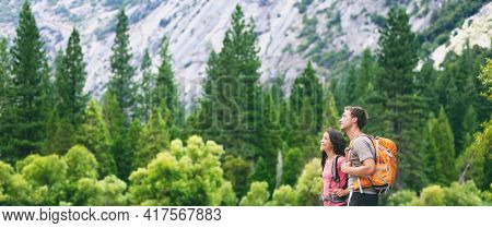 Hikers hiking in outdoor mountain nature landscape looking away to the side copy space on green pine trees forest. Backpacking tourists woman and man couple with backpacks walking outside banner.