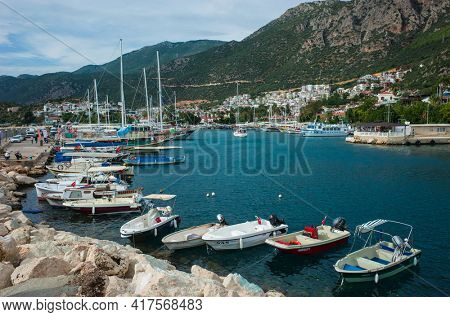 Kas, Turkey - 16 October, 2019: Boats in Kas Marina and rocky mountains on Turkish Mediterranean coast, Popular tourist destination