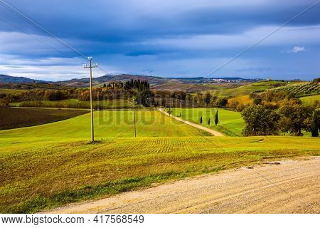 Beautiful Italy. Picturesque hills of the legendary Tuscany. Flat rows of ploughed fields and meadows. Dirt road runs through the hills. The concept of active, rural and photo tourism