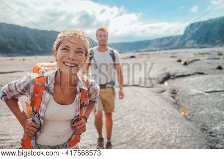 Hiking couple walking with backpacks on lava field trail in Hawaii. Summer travel happy smiling Asian girl and man hikers outdoor adventure on Big Island, USA.