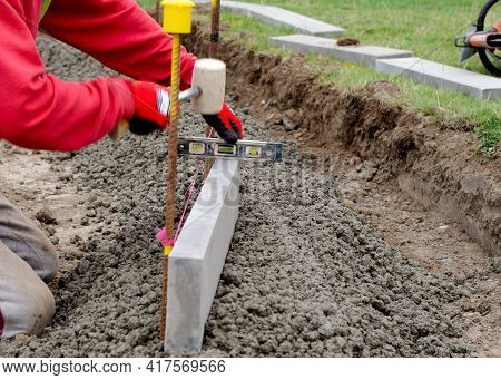 Laing Edging Kerb On Semidry Concrete During Roadworks And New Footpath Construction By Groundworker