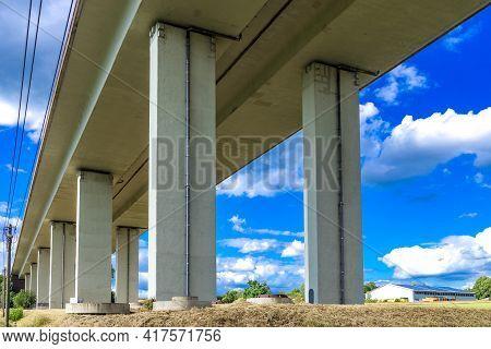 The Pillars Of The Big Modern Bridge Above A Green Grassy Field.