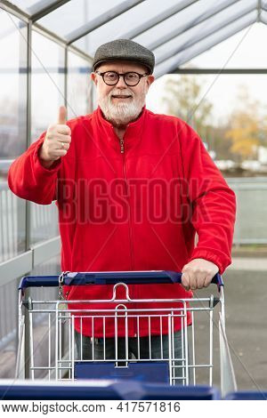 Smiling Senior With A Cap And Red Jacket Pushing A Shopping Cart And Make Thumbs Up