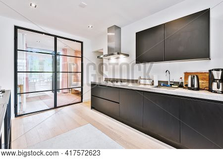 Interior Of Contemporary Kitchen With Stylish Black Cupboards And Appliances Near Dining Area In Con
