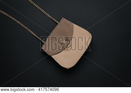 Beige Leather Women's Bag With A Chain Strap On A Black Background. A Fashionable Women's Accessory.