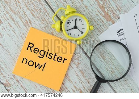 Top View Of Clock, Magnifying Glass And Memo Note Written With Register Now!