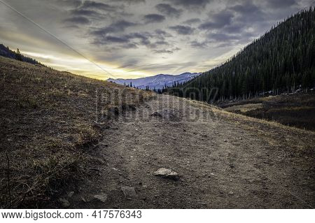 Sunrise Over High Elevation Peaks With Herman Gulch Trail Leading Into The Tree Horizon