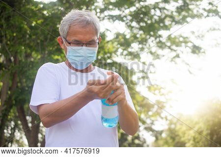 Old Man Wear Medical Mask And Use Alcohol Gel Protect Coronavirus Covid19 At Outdoor City Park