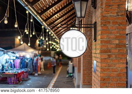 The Circle White Lightbox Has Hung On The Wall In Front Of The Brick Pole In A Tungsten Ambient Envi