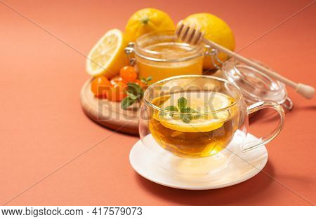 Ginger Tea With Mint And Lemon. Healthy And Hot Drink. Liquid Honey In Honey-jar. Crystal Cup On Bri