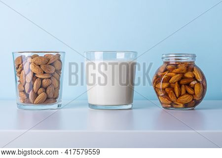 Glass Of Raw Almonds, Vegetable Milk And Jar With Soaking Nuts. Concept Of Making Plant Based Organi